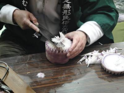 水平にした包丁を構え、くるくると大根を回すと菊の花びらができあがります。